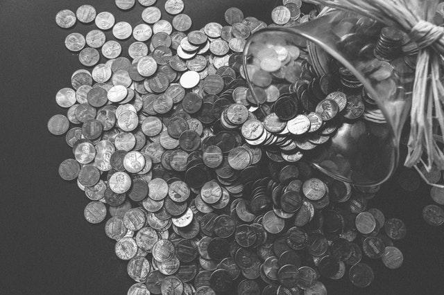 skleněný džbán s rozsypanými stříbrnými mincemi.jpg